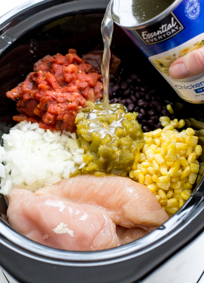 Top shot of enchilada soup ingredients in black slow cooker