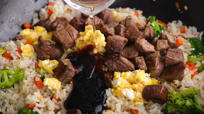 Adding sauce to Beef Fried Rice in black wok