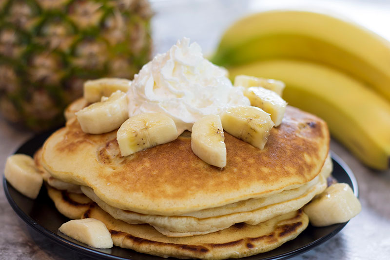 Banana pancakes are delicious with macadamia nuts and honey butter.