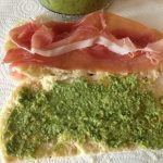 Layered pesto on one side 2 slices proscicutto and  fonitnella cheese on the other side