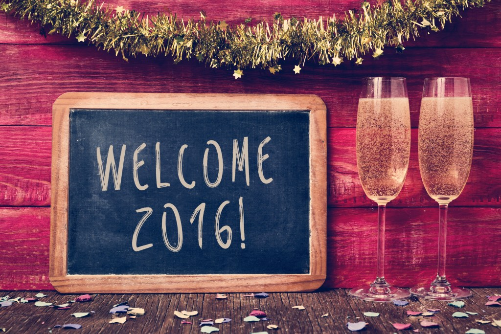 a chalkboard with the text welcome 2016 written in it, some confetti and a pair of glasses with champagne on a red rustic wooden background ornamented with tinsel