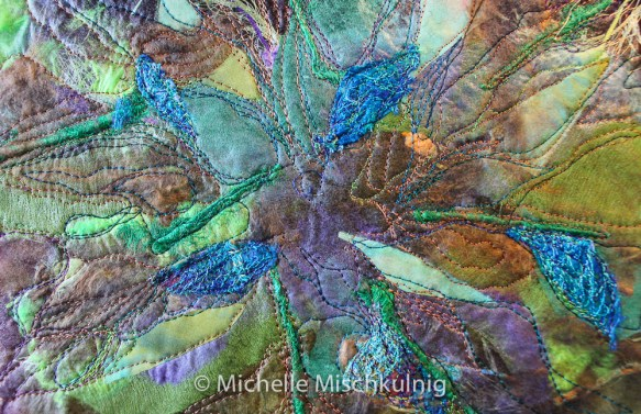 Final layer of texture using blue lace work scraps. Stitching background with different coloured threads.