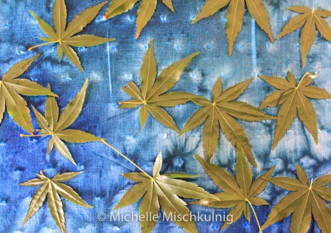 Dye has been painted on a textured cotton then the leaves placed on top.