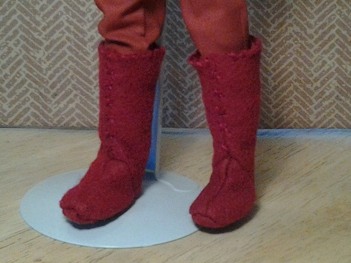 The image shows a pair of doll boots made of rust-colored felt. The doll wearing these boots is a Mattel Ken doll. If you'd like to make these boots, the free printable PDF sewing pattern for these doll boots is found at ChellyWood.com