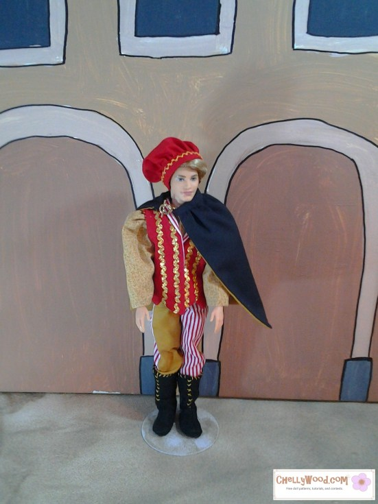 Image of a Ken doll wearing muffin cap, medieval bi-colored pants, boots, a cape, and puff-sleeves.