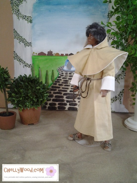 Image of Black doll dressed in wooly wig and wearing a medieval friar's costume, complete with medieval hood, rope sandals, and rosary.
