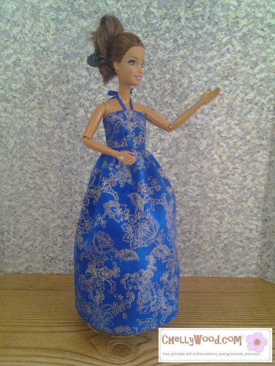 "Image of ""Teresa"" style Barbie doll dressed in handmade blue gown with gold designs. It's in a halter-style with a ribbon that attaches the bodice around the neck. At the bottom of the image it says, ""chellywood.com free tutorials, doll clothes patterns, and more."""