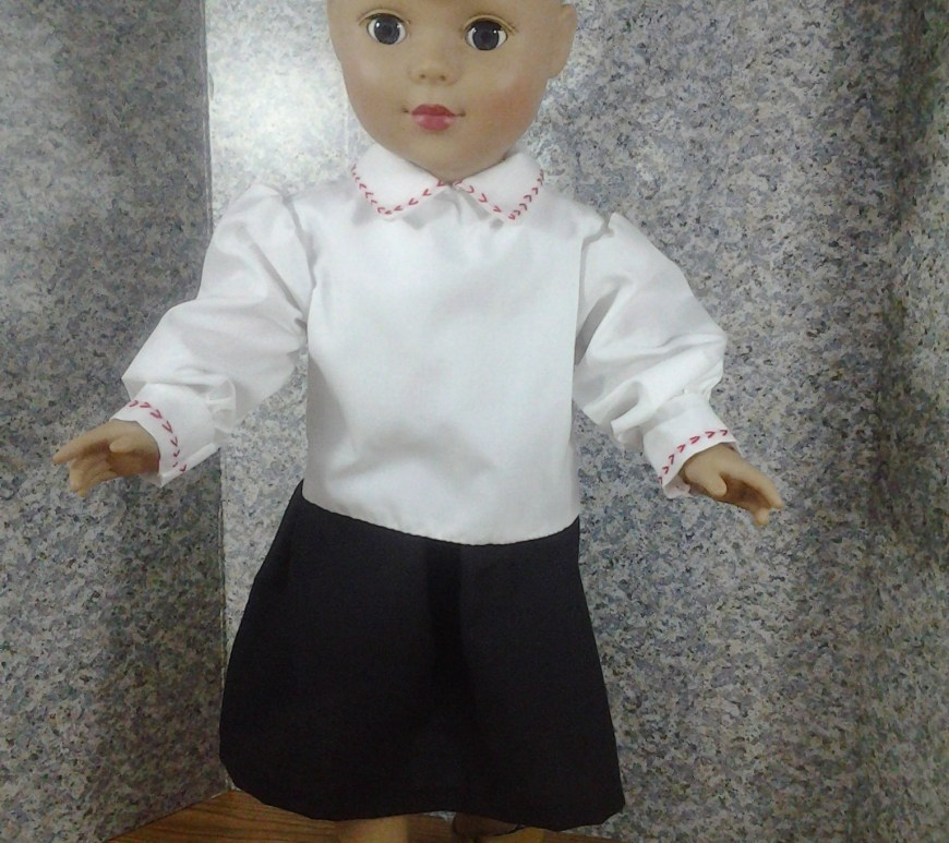 Image of 18 inch doll wearing basic white long-sleeved blouse with basic black skirt.