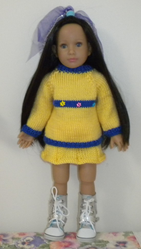 Image of 18-inch doll in yellow sweater with cute flower-shaped buttons across its center stripe