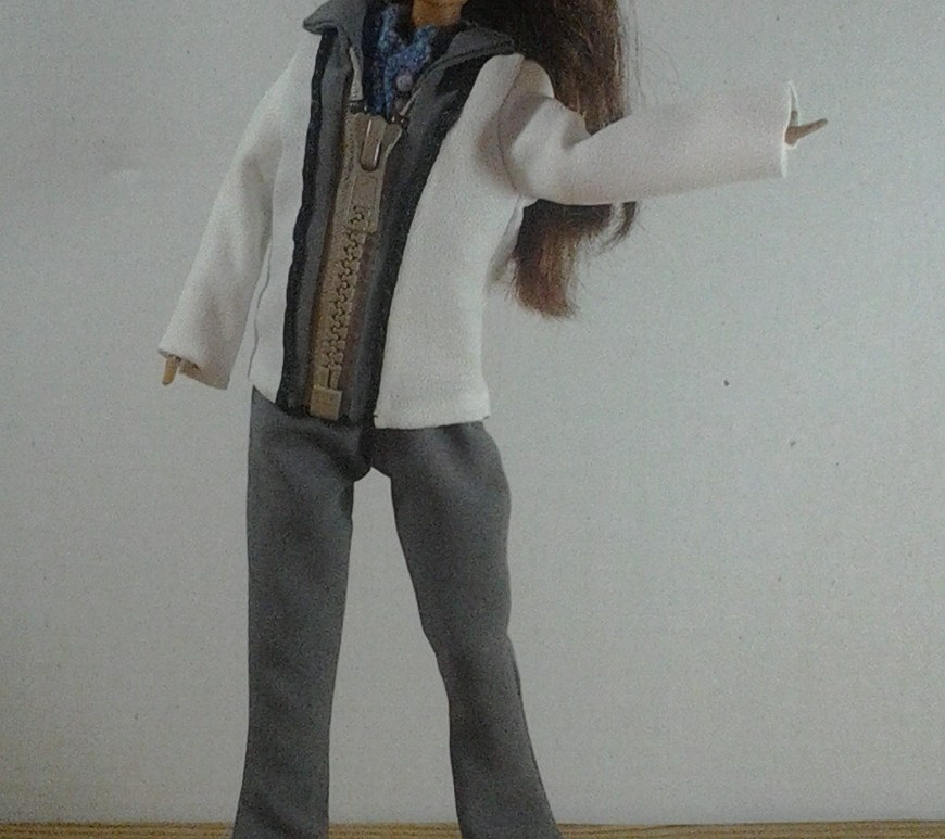 "Image of ""Teresa"" doll from Mattel wearing hand-made zip-front jacket with handmade boot-cut trousers/pants. The doll appears to be waving at the camera."