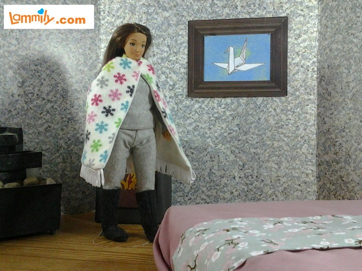 "Image of Lammily's ""Traveler"" doll wearing long underwear, boots, and cape, and standing in a diorama with a bed and Japanese artwork on the wall."