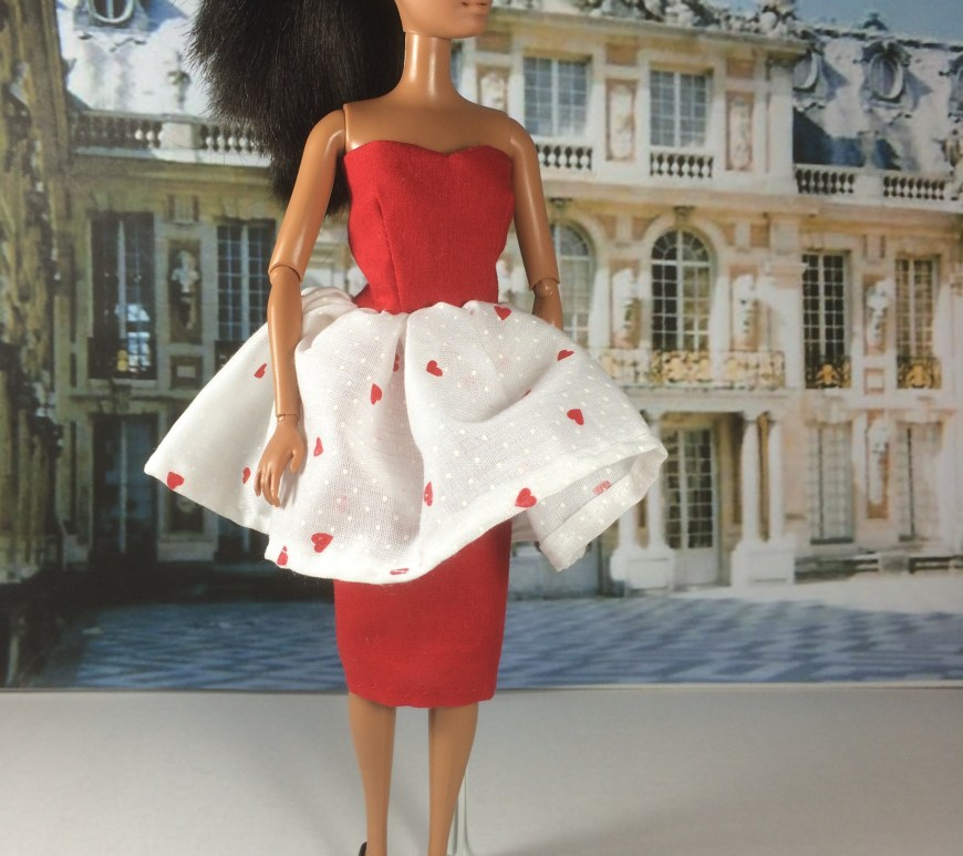 Image of African American Barbie wearing a red strapless dress with flouncy white skirting atop a pencil skirt of red. White flouncy skirt has small red hearts printed on it. FREE Printable Dress pattern for Barbie Dolls