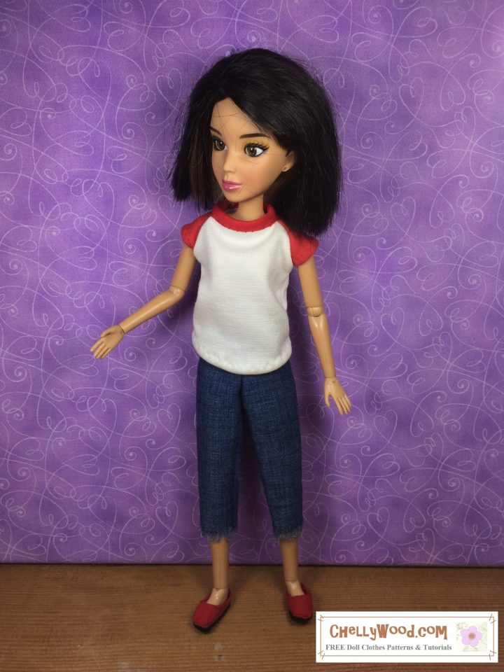Looking for the free printable PDF sewing pattern? Please click in the link provided in the caption. This image shows a Spin Master Liv doll wearing a handmade raglan-sleeve T-shirt and a pair of fringed-edge cut-off ankle pants or capri pants or pedal pusher pants. She also wears handmade shoes.
