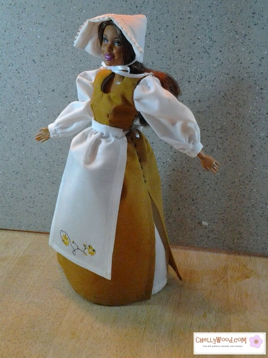Visit ChellyWood.com for free, printable sewing patterns for dolls of many shapes and sizes. Image shows Barbie dressed in a Pilgrim-style dress with apron and bonnet. Apron has daisies embroidered on it.