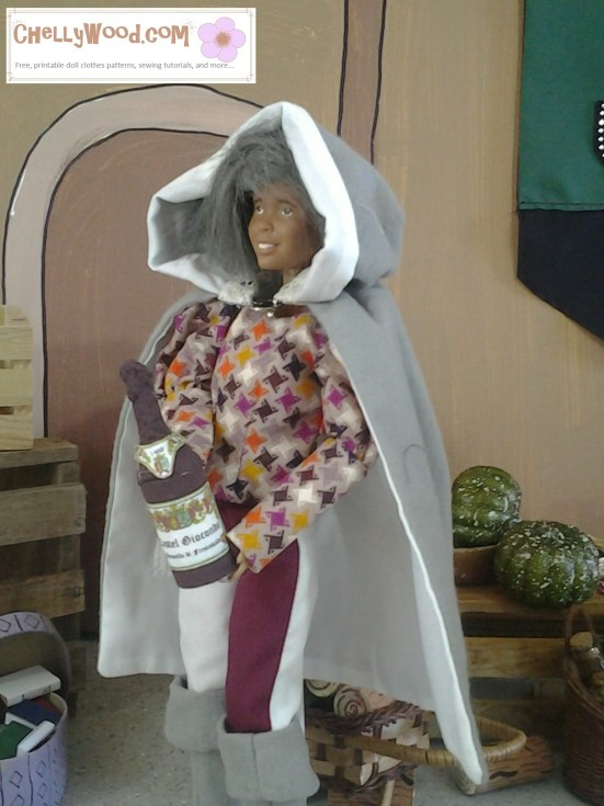 Visit ChellyWood.com for free, printable sewing patterns for dolls of many shapes and sizes. Image shows Barbie in gray wig wearing a harlequin style outfit and medieval or Renaissance-style cape with hood. The doll carries a bottle of wine with tiny labels that have been made to give it more authenticity. Caption reads: Chelly Wood dot com for free printable sewing patterns and tutorials.