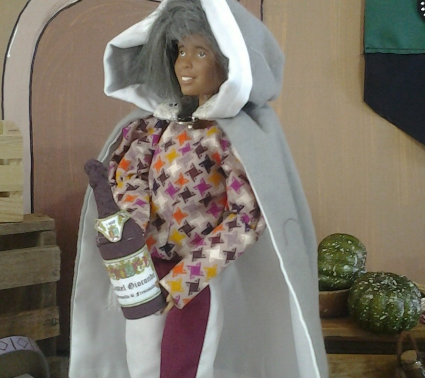 A re-painted Barbie with grey hair wears a pair of bi-colored trousers, a Renaissance jester print tunic, and a cape. She carries a handmade wine bottle. Her character looks male. There's a marketplace diorama behind her.