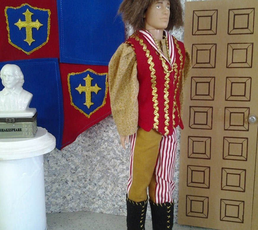 Here we see a Ken doll wearing an auburn wig in a hairstyle that was common during the middle ages. His vest is red with gold rickrack. His puff sleeves are made of floral cotton in a gold print. His bi colored trousers are red and white striped on one leg and gold on the other. He wears black boots made of craft felt. He stands in a ballroom with a bust of Shakespeare behind him. On the wall is a family crest in red and blue cotton hanging with a drape effect. The crest symbol is a gold cross. There's a door to the doll's left, as if he could exit the room whenever he's ready.