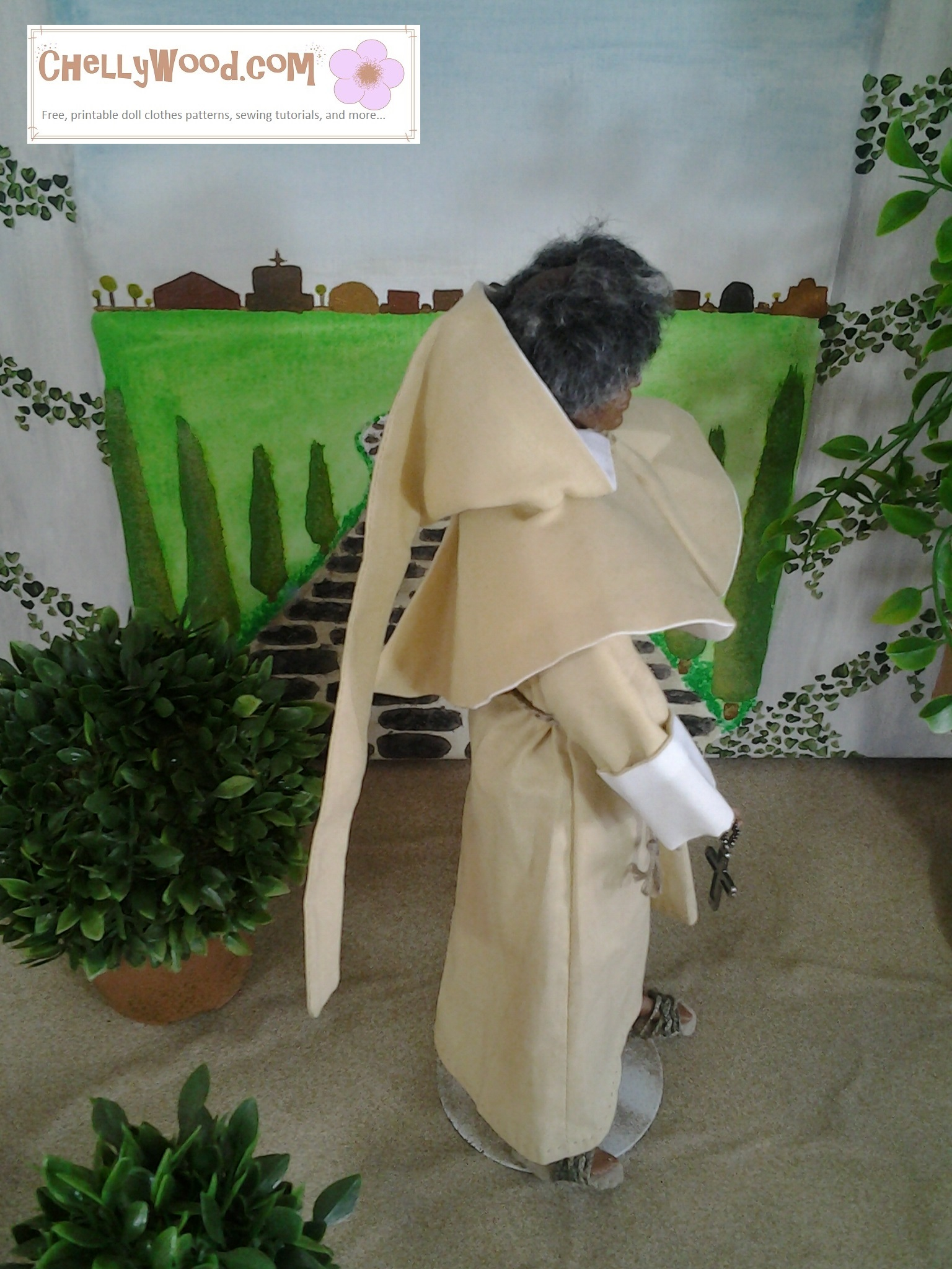 """Image shows Texas A and M Ken doll dressed as Friar Laurence in Shakespeare's Romeo and Juliet. He wears a hooded robe and sandals. He stands in an Italian garden with a cobble-stone path behind him and a small topiary nearby. Caption reads """"Chelly Wood dot come for free, printable sewing patterns and tutorials."""""""