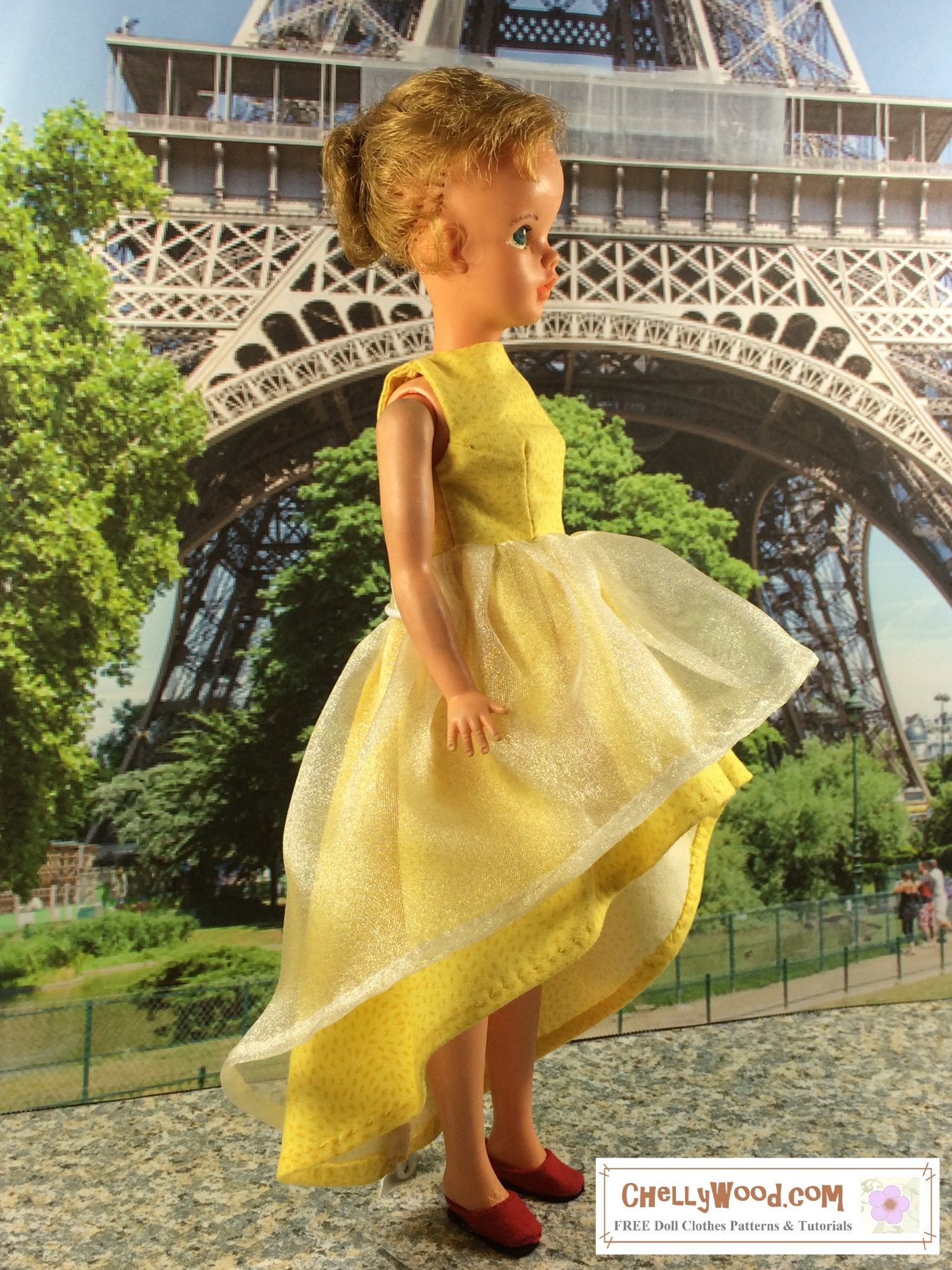 A vintage Tammy doll stands in profile with the Eiffel tower rising behind her. There's a park between Tammy and the towering emblem of France. Tammy has her short hair pulled back into a tiny pony tail with one blond curl sweeping around her tiny doll sized ear. She wears a yellow high low dress (short in front long in back) with a sleeveless bodice and a glistening layer of tulle over the top of the yellow skirt.