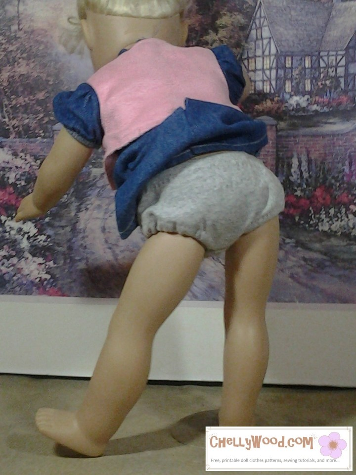 The image shows an 18 inch doll (like American Girl) facing away from the camera. The edges of her little denim skirt have slipped up, exposing her grey jersey fabric underpants in a way that's very obviously accidental.