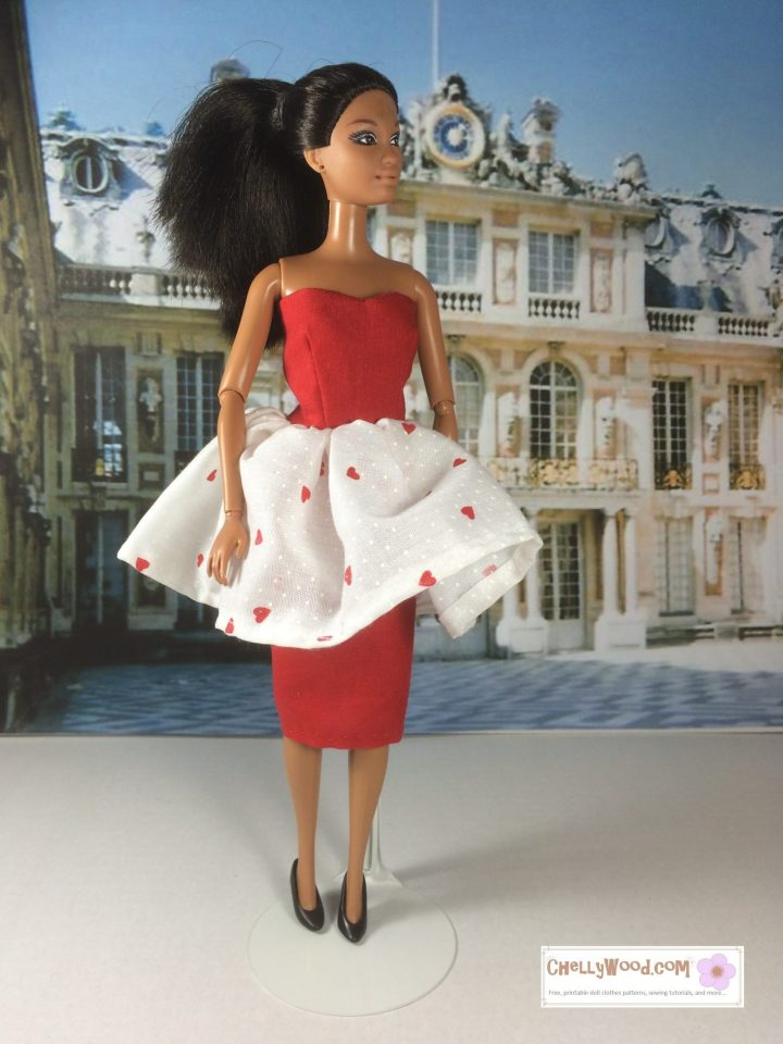 The image shows a Mattel Barbie doll wearing a red pencil-skirt-dress-with-overlapping-flouncy-skirt. She stands in front of Versailles, a castle in France. The handmade dress she wears is strapless in the colors red and white. Would you like to make this garment? Please click on the link in the caption for the free printable PDF sewing pattern and links to several helpful tutorial videos.