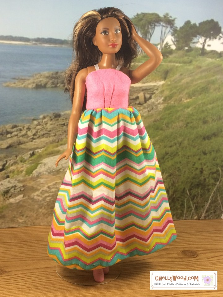 Click on the link in the caption to navigate to the page where you can download and print a free printable PDF sewing pattern for making this super easy summer sun dress (sundress) to fit your Curvy Barbie doll or similar sized dolls. The image shows a Curvy Barbie doll wearing a handmade doll dress with a long skirt made of cotton; the dress also has an easy-to-sew felt bodice of pink felt with ribbon straps.