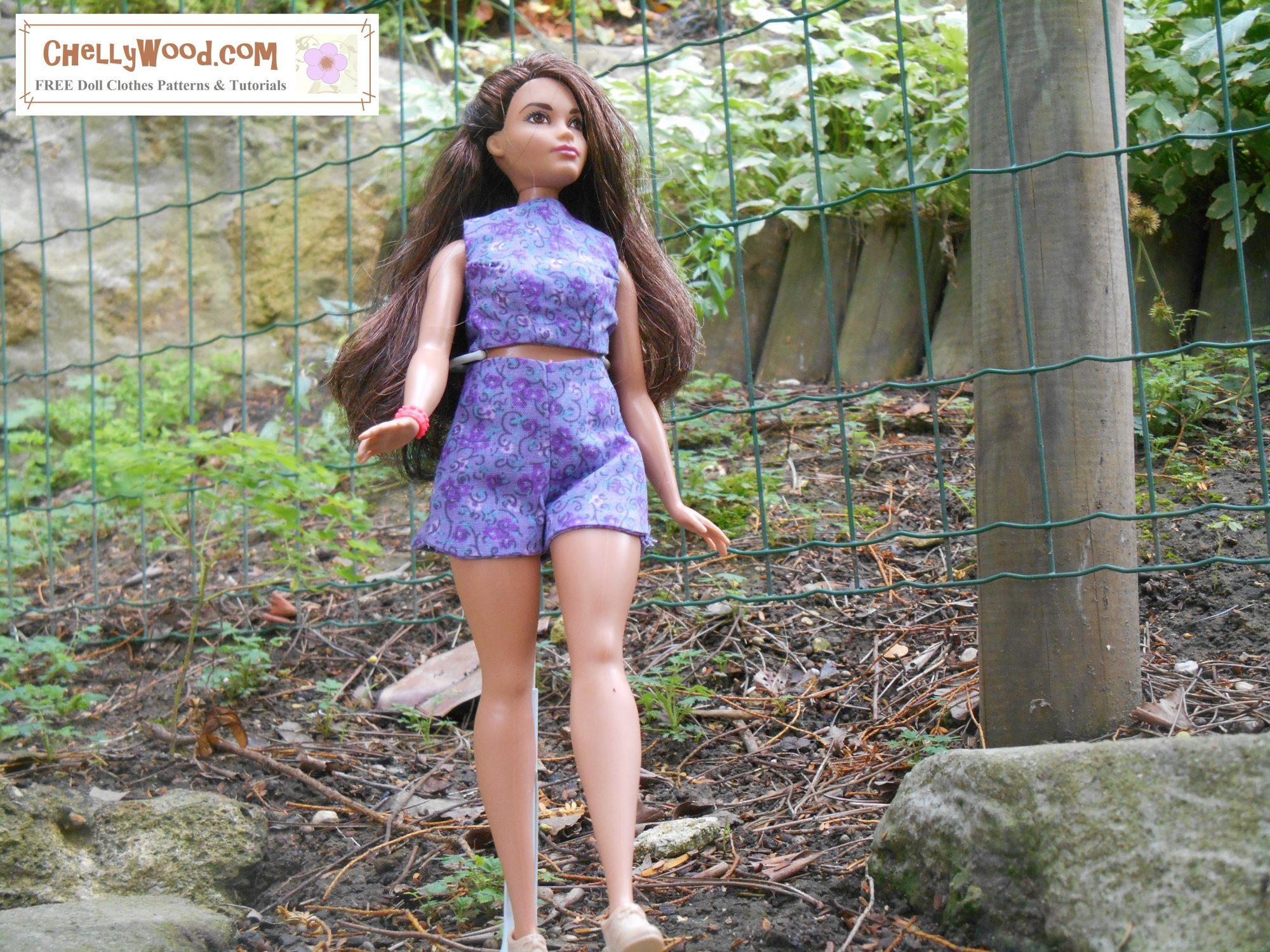 The image shows a Curvy Barbie walking in a garden. She wears handmade high-waisted shorts and a handmade crop top. The purple floral cotton fabric of her shirt and shorts contrasts against the green background of the garden. The overlay reminds you to visit ChellyWood.com for your free printable PDF sewing patterns for making this adorable summer outfit for Curvy Barbie dolls and similar sized dolls.