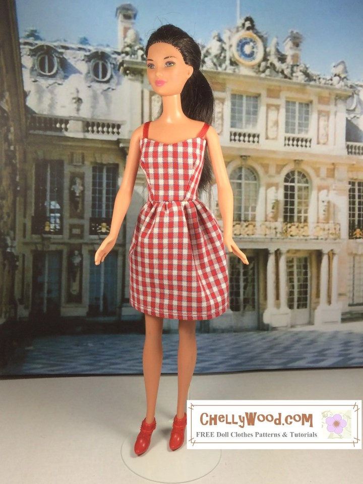 The image shows a short, above-the-knee-length gingham dress in red and white check with red ribbon straps. The doll appears to stand before the Château de Versailles.