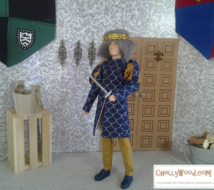 The photograph shows a Ken doll wearing a grey wig and a royal crown. He stands in a castle diorama holding a sword upright. His navy colored tunic has Renaissance puffy sleeves and his tunic has a gold lattice print. His trousers are made of gold cotton fabric to match the print of his tunic. His shoes match the navy blue background color of his tunic.