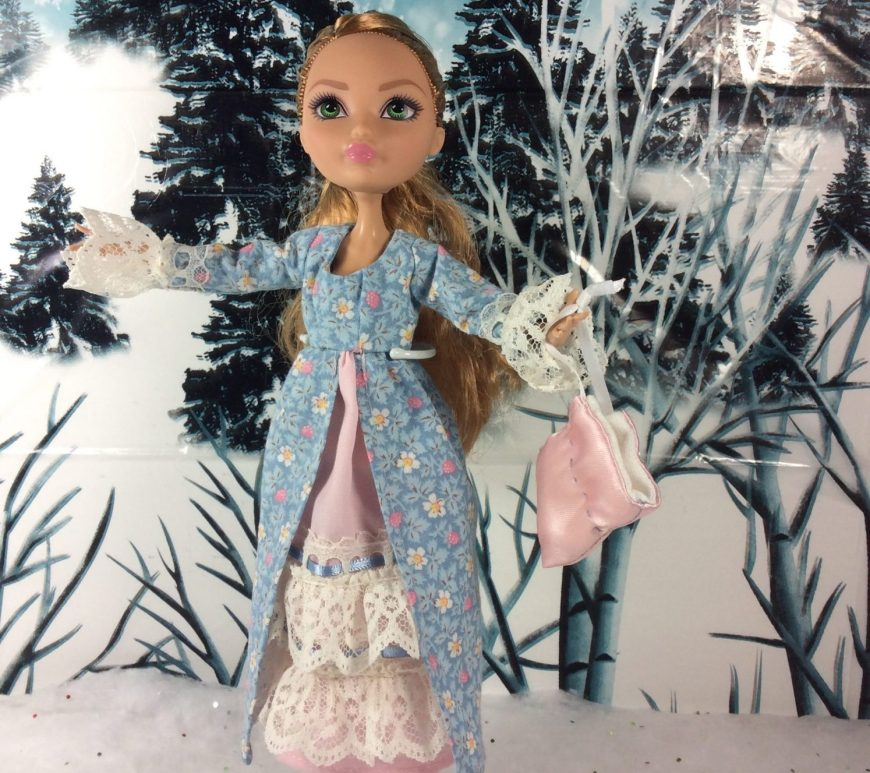 The photo shows a lovely female Ever After High doll wearing a pretty pioneer style dress with lace sleeves and lacy petticoats. The doll stands in a snowy diorama holding a drawstring purse made of pink satin. The dress is made of blue cotton with pink cotton petticoats trimmed in white lace and blue ribbons.