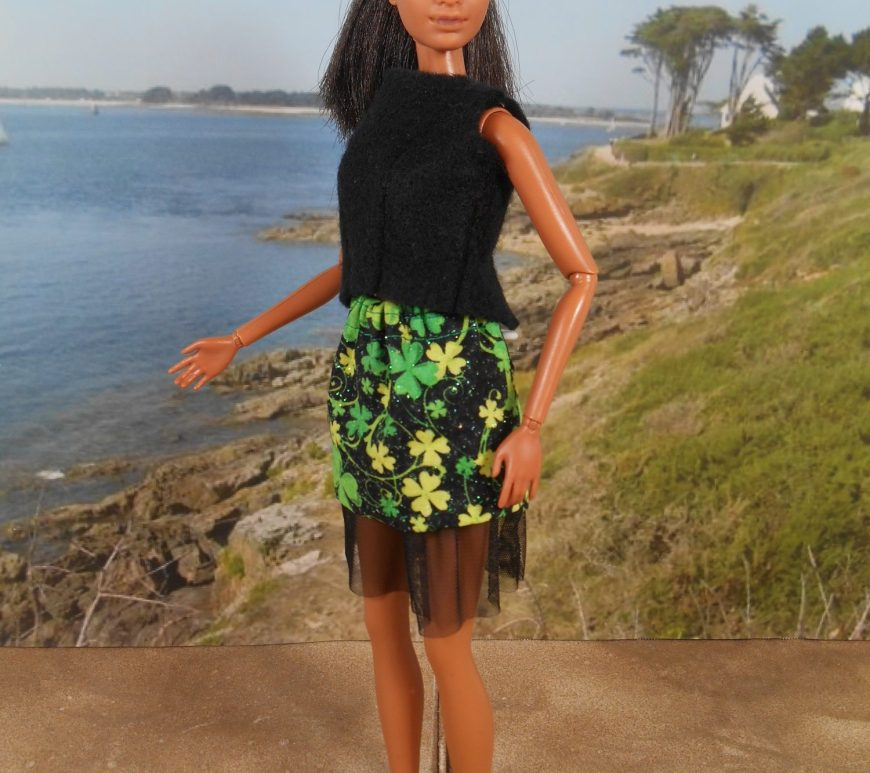 Mattel's Barbie models a black felt shirt with a short shamrock black-and-green print cotton skirt that has a layer of tulle under it. The doll stands on the sand at a beach with the coastline behind her.