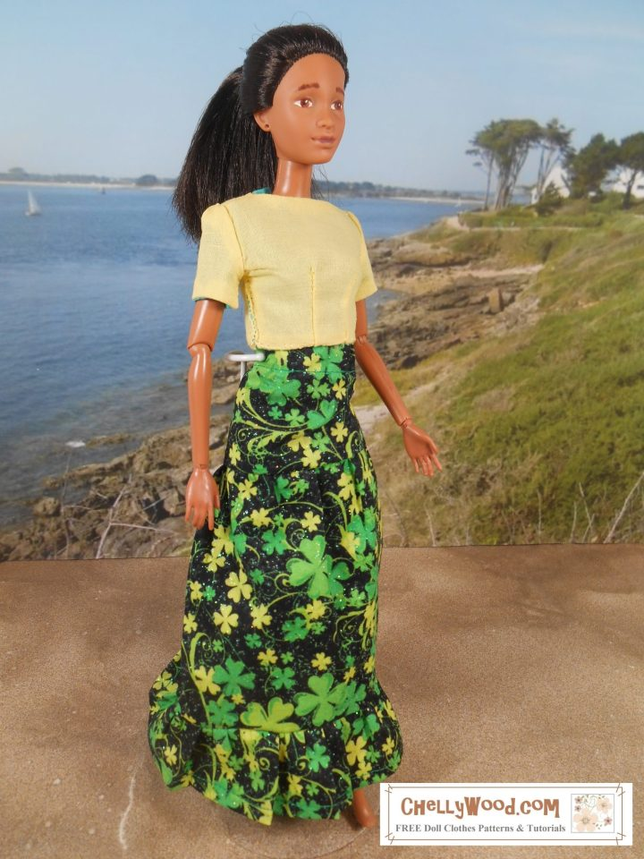 On a beach setting, we see a Mattel Barbie doll wearing a green, black, and yellow maxi skirt decorated with shamrocks and a reversible yellow shirt with short sleeves.