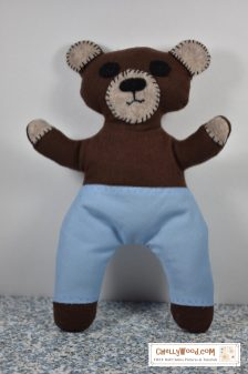 The image shows a hand-embroidered firefighter bear in a facsimile of Smokey the Bear. His face and other parts of this stuffed animal are hand stitched and embroidered. This embroidery and sewing project can be found at ChellyWood.com including free printable sewing patterns and tutorial videos.