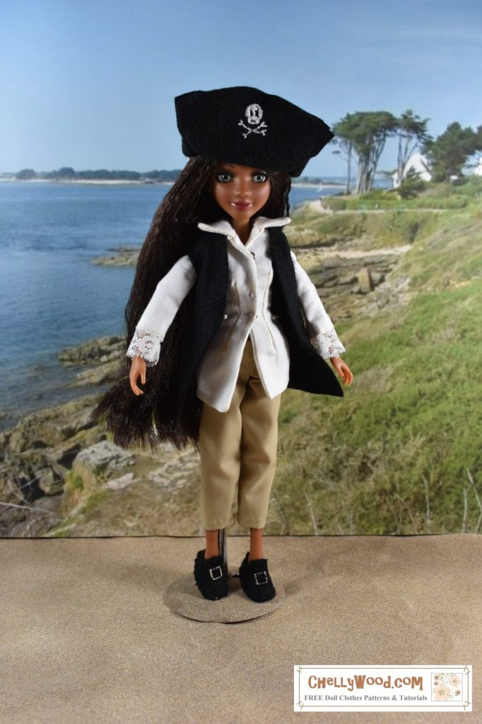 A Project MC Squared Bryden Bandweth doll models a pirate costume while standing on a sandy beach with a harbor behind her. Her black felt tricorn hat has a Jolly Roger embroidered on the front flap. Here folded collar long shirt has lace edges along the sleeve openings. She wears a black felt vest and a pair of short trousers. Her shoes are black felt Colonial style shoes with big silver buckles.