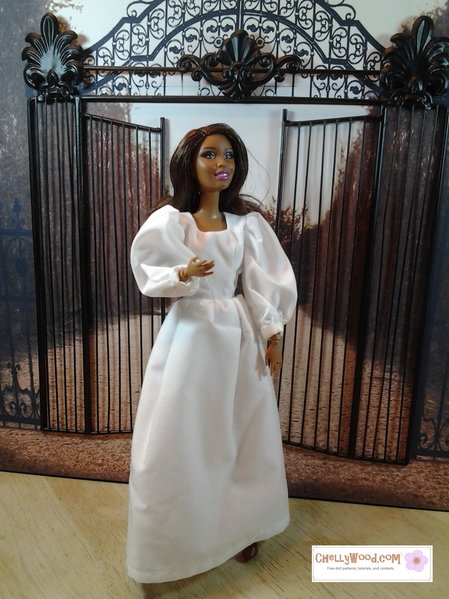 This is a photograph of an African American Barbie doll standing in front of a garden gate, wearing a shift gown with puffy sleeves and a narrow waist. This basic dress pattern is used for the undergarments in a number of Renaissance dress costumes on the ChellyWood.com website (for fashion dolls).