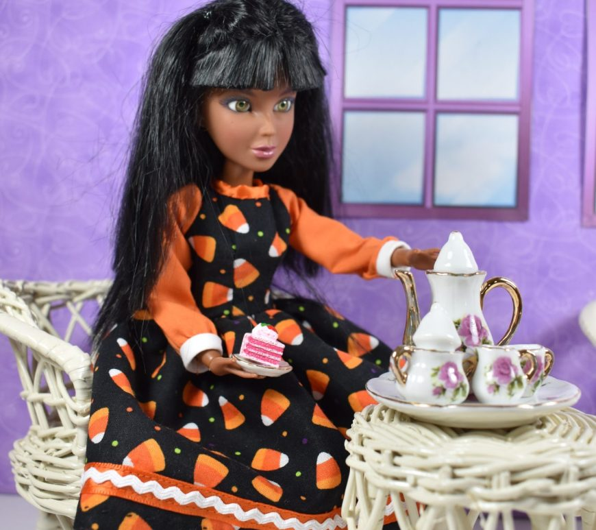 Here we see a Spin Master Liv doll sitting in a wicker chair, in a purple room. She's reaching out to a tray of tea with a teapot, which rests on a white wicker table. In her lap is a tiny china plate of pink cake. Her dress has orange sleeves and white cuffs but the largest part of the dress, including the bodice and skirt, are made of black fabric decorated with tiny white and orange candy corns. The skirt's hem is embellished with orange ribbon and white 1/8 inch rickrack trim.