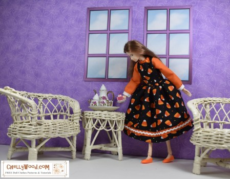 The image shows a Momoko doll dressed in a Halloween-print candy corn doll dress with cuffs at the end of long sleeves. She's in a tiny diorama with windows and wicker furniture. On the wicker table is a tea set. If you'd like to make the dress shown, please click on the link in the caption.