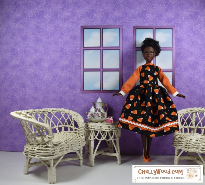 In a room with purple walls and a white floor, a Petite Barbie stands poised elegantly in front of two windows. To her right is a  white wicker love seat and a white wicker table loaded with a tiny porcelain tea set. To her left is a matching white wicker chair. She wears a handmade Halloween party dress made of cotton. The sleeves of the dress are rich orange with white cuffs. The body of the dress and the skirt are made of black fabric dotted with tiny candy corns. The skirts hem is edged with orange satin ribbon overlaid with tiny one eighth inch rickrack trim. The doll is African or African American with a deep chocolate complexion. Her bright orange plastic shoes tie the whole outfit together, bringing out the orange in the candy corn print and the orange of the sleeves.