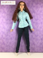 On a purple background, a Tonner doll models a pair of skinny jeans and a floral jacket with a collar.