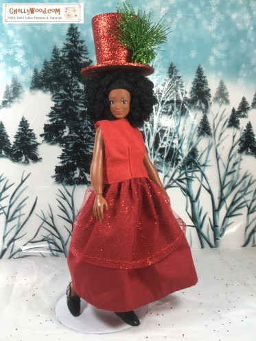 """The image shows a Lammily Photographer doll dressed in a red New Year's Eve party skirt and sleeveless """"sweater"""". The """"sweater"""" is made of felt and has darts in the front. It looks super easy to sew! The skirt has a layer of red cotton skirt and an over-layer of glittery-red tulle skirting. The doll wears a red glitter top hat embellished with a glittery green pine sprig. She stands in a snowy diorama with pine trees in the distance behind her. Snow is falling. The watermark says, """"ChellyWood.com FREE printable patterns and tutorials."""" If you would like to download all the free printable sewing patterns and listen to or watch the tutorials for making this outfit for your Lammily or similar-sized dolls, please click on the link in the caption."""