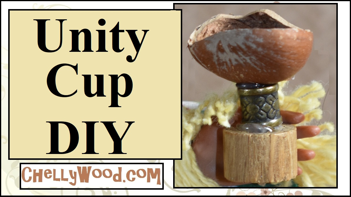 The image shows a handmade unity cup for Kwanzaa in 1:6 scale for dolls like Barbie and Ken. The cup appears to be made from a cylindrical bead, a slice of dowel rod, and half of a hazelnut. A small doll hand holds the cup aloft.