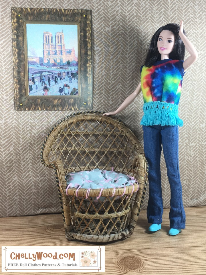 Image shows Mattel's Tall Barbie from the Fashionista line wearing a pair of hand-made bell bottom jeans (boot cut jeans) with a tie dye shirt. She poses in front of a painting of the Notre Dame cathedral in Paris (a facsimile of the famous painting by Monet), and she stands beside a wicker papasan chair with a handmade gray and pink cushion that has been upholstered with 1:6 scale buttons.  The Tall Barbie's expression looks cheerful and spontaneous, like someone took the photo unexpectedly.