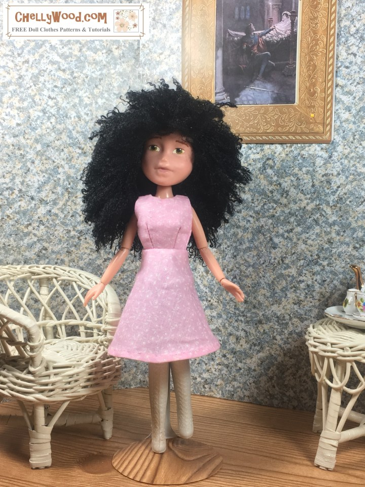 """Image shows 10"""" Bratz doll wearing an handmade A-line dress and standing in a 1:6 scale diorama that shows the bust of a musician, a classical painting, and is decorated with a wicker table and chair. On the table is a 1:6 scale porcelain tea set for little dolls. The 10"""" Bratz doll wears a dress that has been sewn by hand. Overlay offers the sewing tutorials and free doll clothes patterns website: ChellyWood.com and states that this website has free doll clothes patterns and tutorials for dolls of many shapes and sizes."""