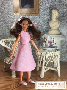 """The image shows a Mego Wizard of Oz Action Figure doll wearing a handmade A-line sleeveless dress for tiny-body 8"""" or 9"""" inch dolls like Mego Wizard of Oz Action Figure dolls. In the diorama where the Mego Wizard of Oz Action Figure doll stands, there's a tiny tea set on a wicker table, a wicker chair, and a bust of a musical composer resting on a pedestal. The patterns for making this A-line dress for Mego Wizard of Oz Action Figure dolls are found at ChellyWood.com as a PDF downloadable sewing pattern. Chelly Wood designs free printable sewing patterns for making doll clothes to fit dolls of many shapes and sizes. Go to ChellyWood.com for both the PDF pattern and free tutorial video giving instructions for making this lovely dress which will fit Mego Wizard of Oz Action Figure dolls and other similar-sized dolls."""