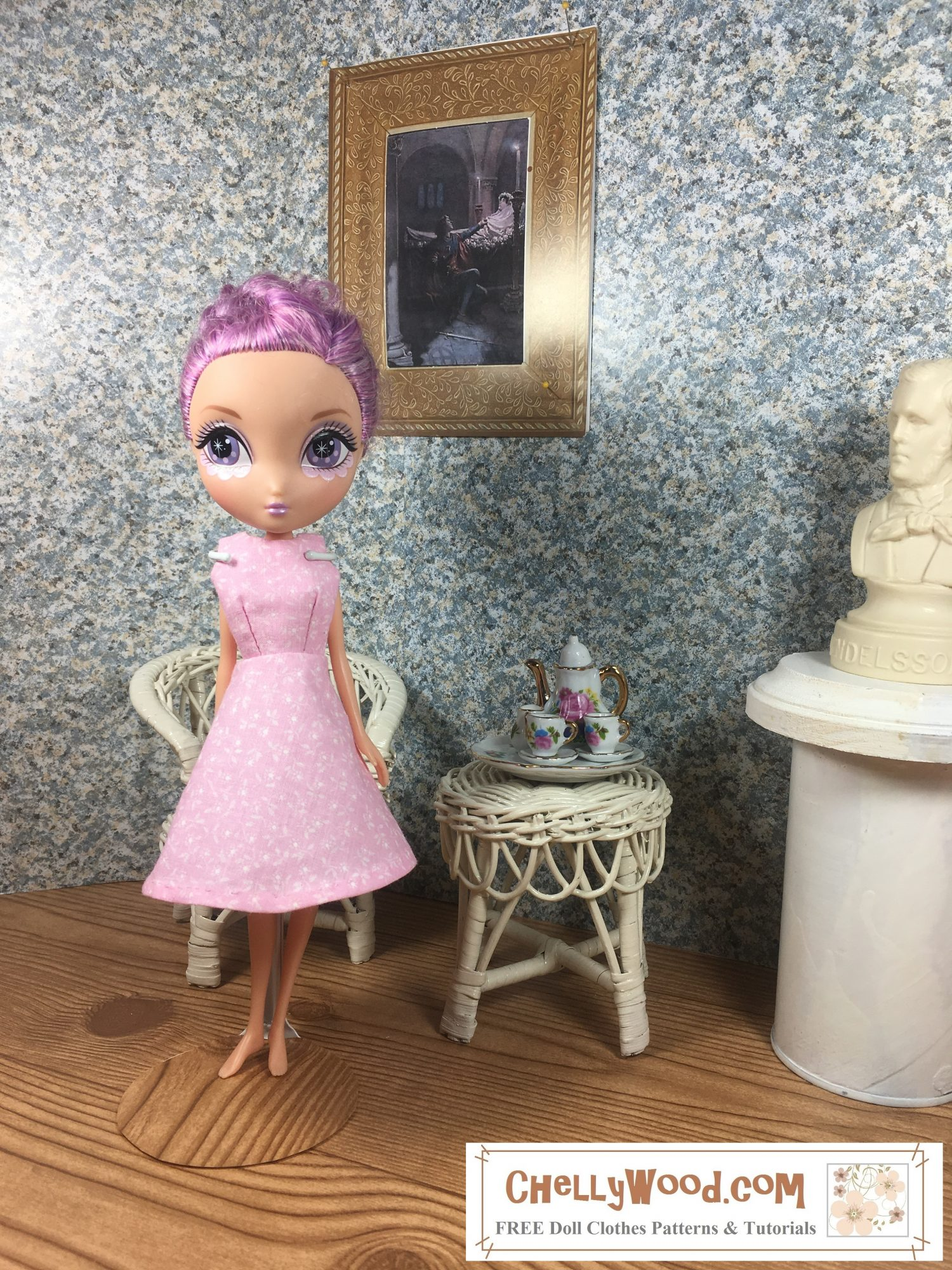 """A Spin Master La Dee Da doll with lavender colored hair stands in a ballroom beside a wicker table that holds a tiny tea set decorated with miniature pink flowers. She stands in front of a matching white wicker chair. On the wall behind her is a gold-framed miniature painting of Romeo and Juliet. Off to the side is a bust of a composer. The doll wears a handmade A line dress made of pink floral cotton. It's a sleeveless dress with a skirt that flares out from just above the waist to just below the doll's knee. She stands with her weight on one let, hands behind her back, in a big eyed pose that says, """"I'm shy!"""""""