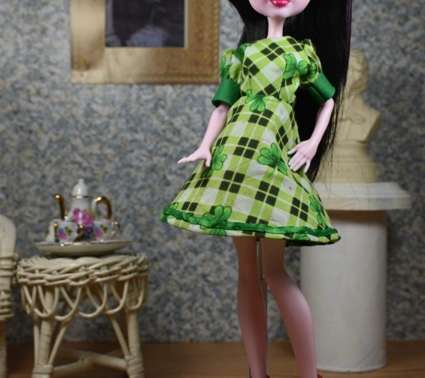 This photograph shows a Draculaura doll in an elegant ballroom where a tea set rests on a wicker table beside a wicker chair. There's a bust of a famous composer (impossible to tell which one) directly behind her. Also at her back is a famous painting of Romeo and Juliet framed in gold. The doll stands with one hand on her hip, which makes her A line dress skirt seem even more bell like. The dress she wears has Kelly green cuffs and a green and black tiny plaid pattern. The skirt of the dress is embellished with Kelly green ribbon. The short cuffed sleeves are slightly puffed.