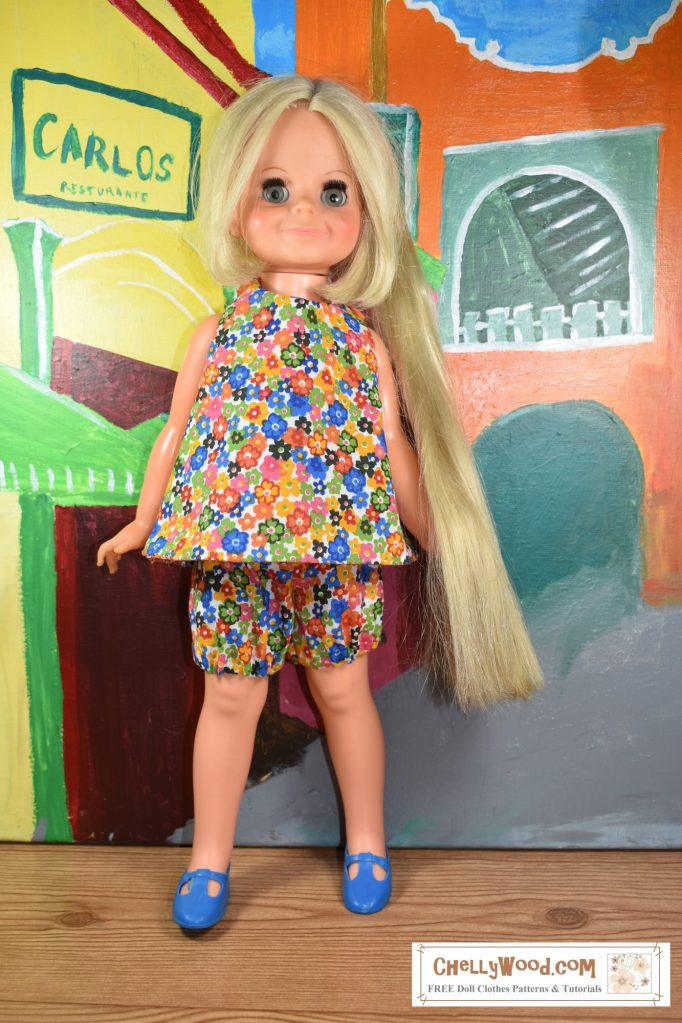 Here we see a vintage Velvet doll standing in a street in a colorful Caribbean village. The colors in her floral halter dress and bloomers (panties) match the bright colors on the buildings behind her.
