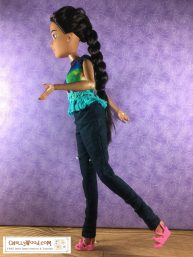A 17 inch dreamtopia endless hair kingdom princess Barbie doll appears to be in the process of walking along, wearing a pair of snug jeans and a tie dyed sleeveless shirt with a fringe of embroidery floss at the bottom.