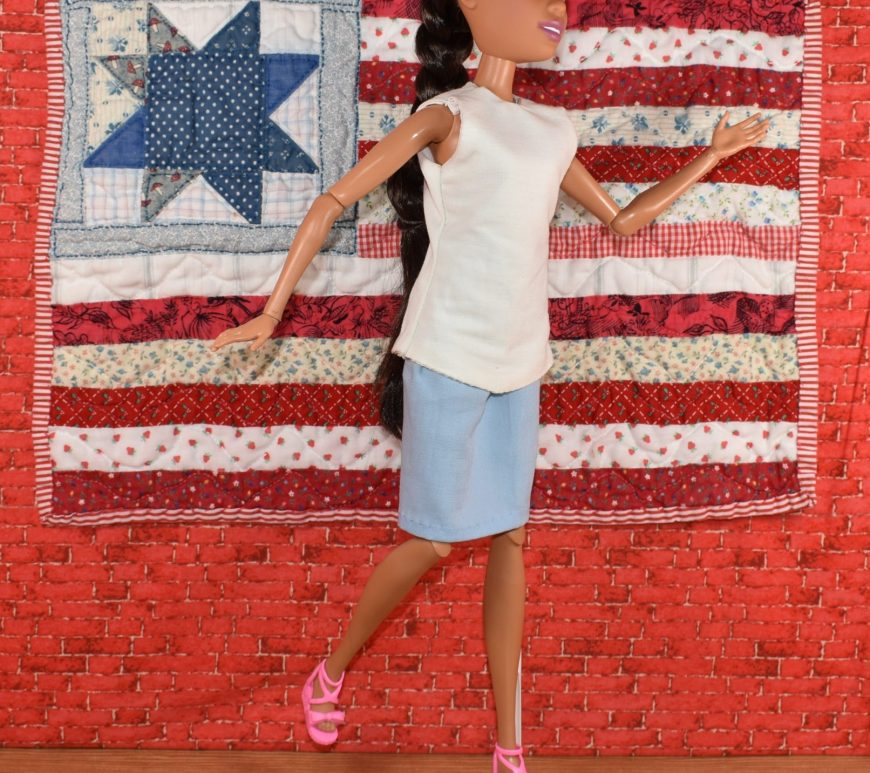 A 17 inch Dreamtopia Endless Hair Kingdom Barbie walks past a quilted American flag hanging on a brick wall behind her. the doll wears a sleeveless white summer top with a blue business skirt and pink plastic shoes.