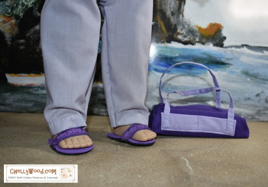 "Image shows the 18"" or 46 cm doll from the Madame Alexander Doll company wearing hand-sewn pants and DIY sandals. The image is a close-up of her feet and legs. She carries a handmade gym bag that matches her outfit. She stands on a sandy beach with a seascape behind her including rocky cliffs and rolling waves. This 18"" or 46 cm Madame Alexander Doll has set her DIY gym bag down in the sand as if she's getting ready to have some fun at the beach today. The header for the image says, ""Purple gym Bag Pattern for AG Dolls FREE 2"" and the watermark says, ""ChellyWood.com: FREE doll clothes patterns and tutorials."" In fact, if you go to ChellyWood.com, you can download the free, printable sewing pattern for this gym bag (and the other Madame Alexander -sized doll clothes patterns for the other items of clothing she wears) and all patterns at ChellyWood.com are free and come with a free tutorial video showing how to make the clothing item (including this gym bag or overnight bag for dolls)."